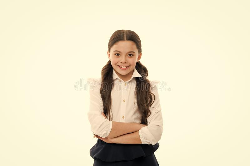 A giggling schoolgirl. Adorable little schoolgirl with happy smile keeping arms crossed. Small schoolgirl looking nice stock image