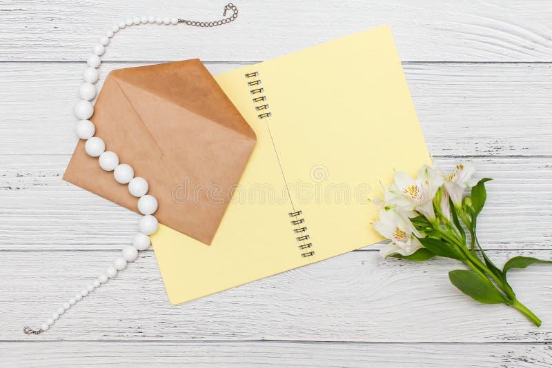 Gigli bianchi con il taccuino giallo e perle con la busta del mestiere sulla tavola di legno bianca, vista superiore, disposizion immagini stock