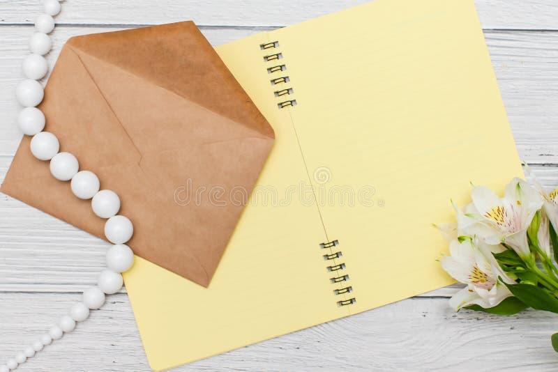 Gigli bianchi con il taccuino giallo e perle con la busta del mestiere sulla tavola di legno bianca, vista superiore, disposizion fotografia stock libera da diritti