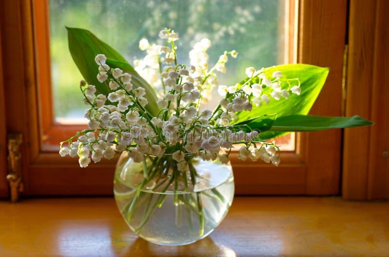 Gigli di maggio in un vaso di vetro fotografia stock