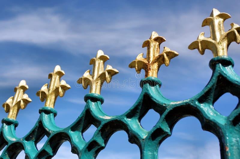 Giglio araldico dell'oro sulle inferriate blu del ferro immagine stock libera da diritti