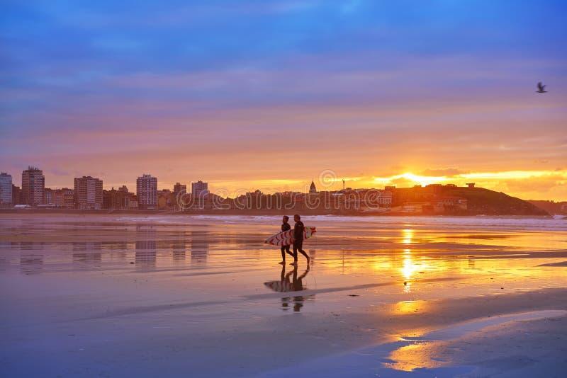 Gijon日落圣洛伦佐海滩冲浪者在阿斯图里亚斯 图库摄影