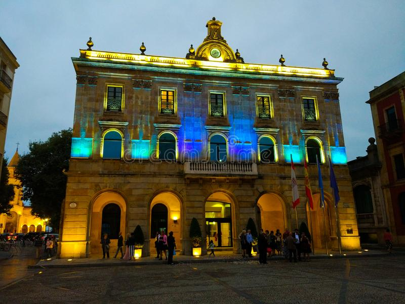 Gijon,阿斯图里亚斯,西班牙有启发性城镇厅,有蓝色光的夜间 库存图片