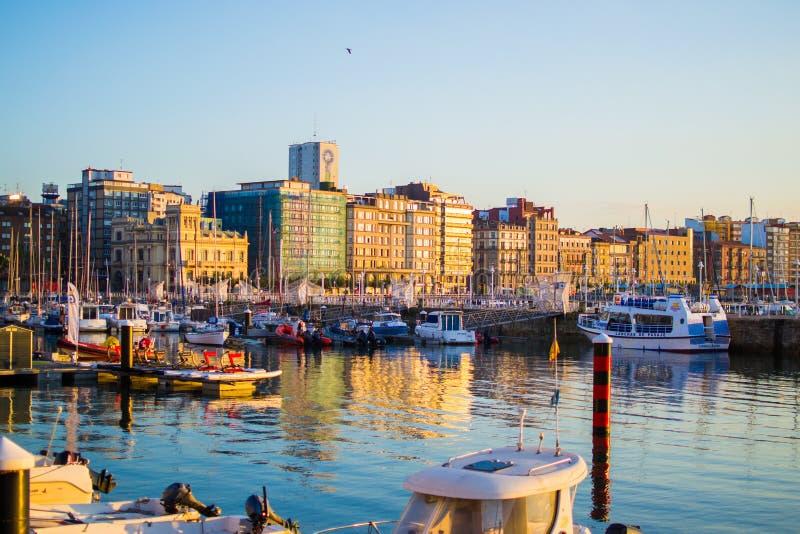 Gijon, as Astúrias, Espanha; 09/26/2018: Por do sol na doca de Gijon, as Astúrias, Espanha Reflexões dos barcos na água imagens de stock royalty free