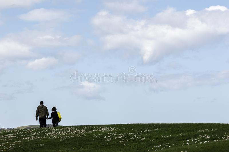 Gijon, Asturies, Espagne, le 9 avril 2019, couples supérieurs marchant le long de parler heureusement en parc avec un ciel bleu photographie stock libre de droits