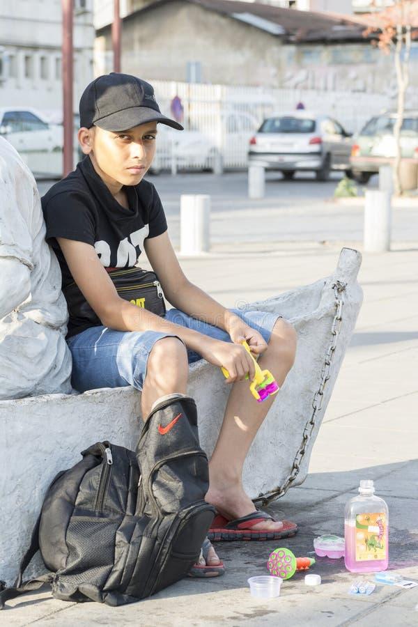 Gilan省卖泡影制造商的一个年轻少年的伊朗6月10日2019年画象在街道垂直的射击 库存照片