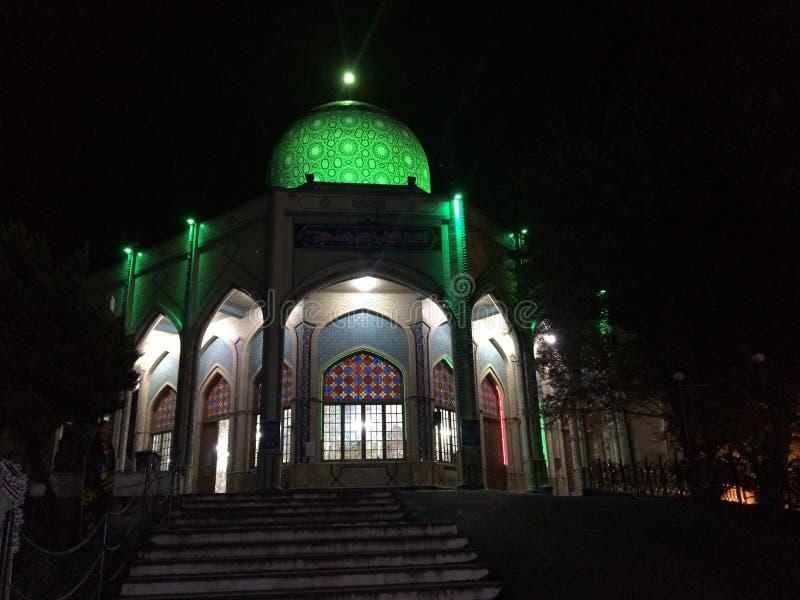 Gilan, Irã - verão, 2018: O santuário da imã Zadeh Hashem fora da cidade de Gilan, abóbada clara verde na obscuridade da noi imagens de stock