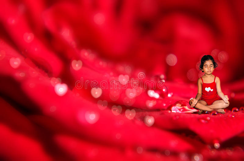 Girl child meditating on macro rose flower royalty free stock photography