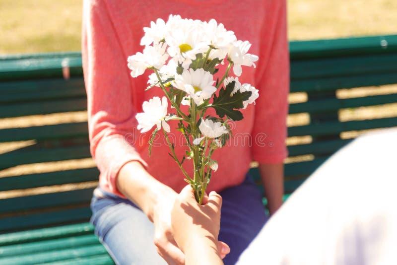 Gilde die bloemen geven aan moeder stock afbeeldingen