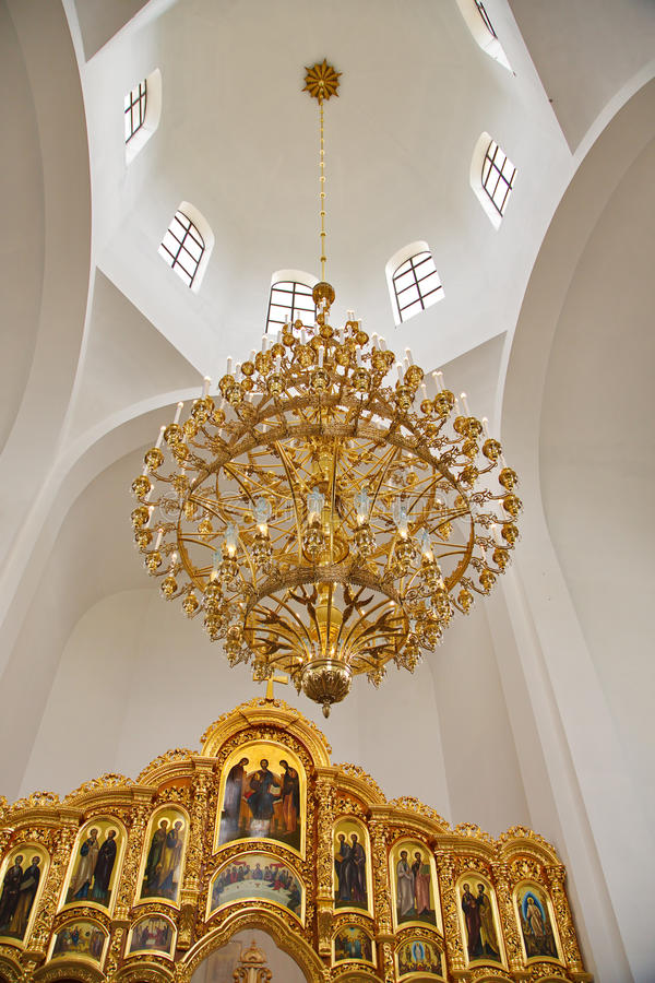 Gilded chandelier under the dome of the Christian church. Large gilded chandelier under the dome of the Christian Orthodox church. White arch dome illuminated royalty free stock images