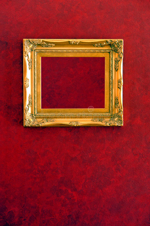 Gilded Gold Frame on Red Wall Background royalty free stock image