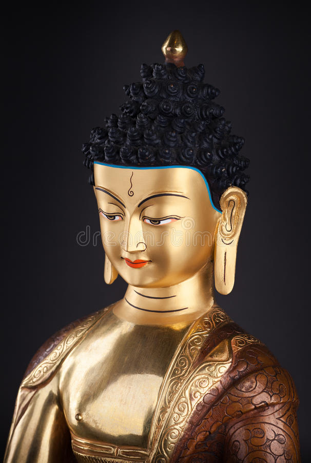 Gilded head of Buddha. The top part of a gilded statue of Buddha, in traditional clothes with ushnishy on the head. Isolated on black background royalty free stock images