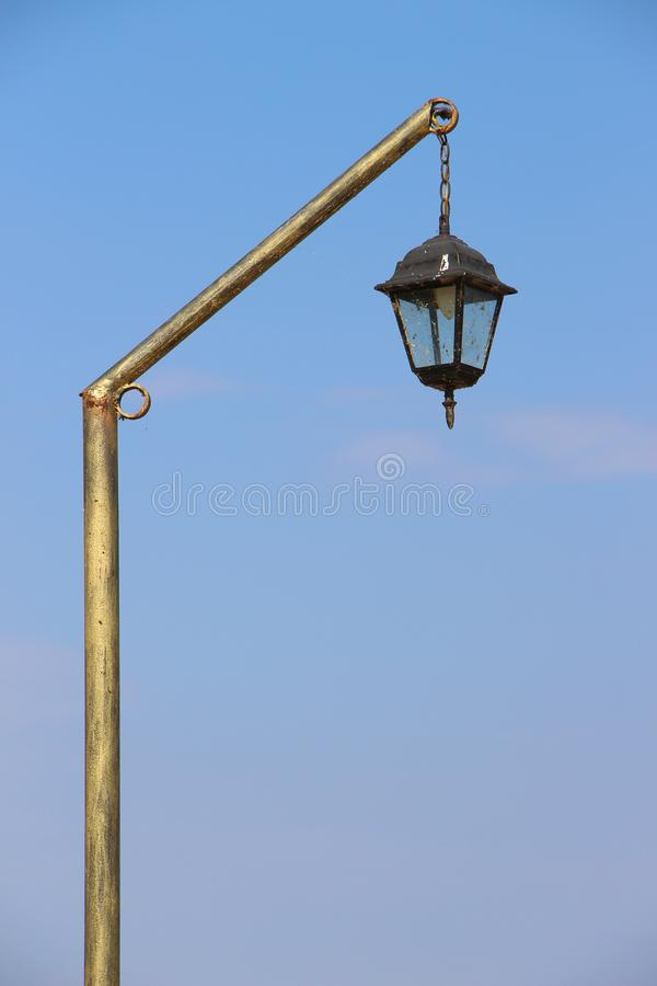 Gilded old vintage street lantern isolated on blue sky with copy space for text stock photo