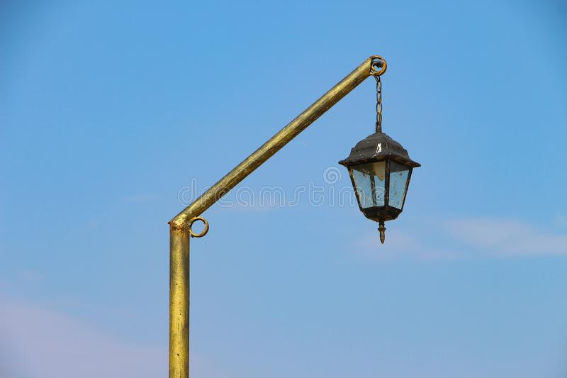 Gilded old vintage street lantern isolated on blue sky stock photo