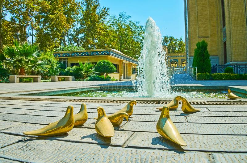 The gilded pigeons at the fountain, Tehran, Iran. TEHRAN, IRAN - OCTOBER 25, 2017: The sculptural composition of gilded pigeons at the fountain in garden of stock photo