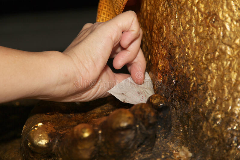 Gilding gold leaf to Buddha for worship. Selective focus. royalty free stock image