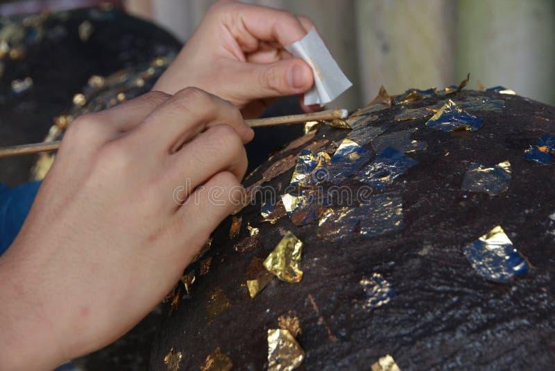 Gilding gold leaf to round stones embedded for worship Buddha. Buddhists make merit,Gilding gold leaf to round stones embedded ,call LukNimitr , for worship royalty free stock images
