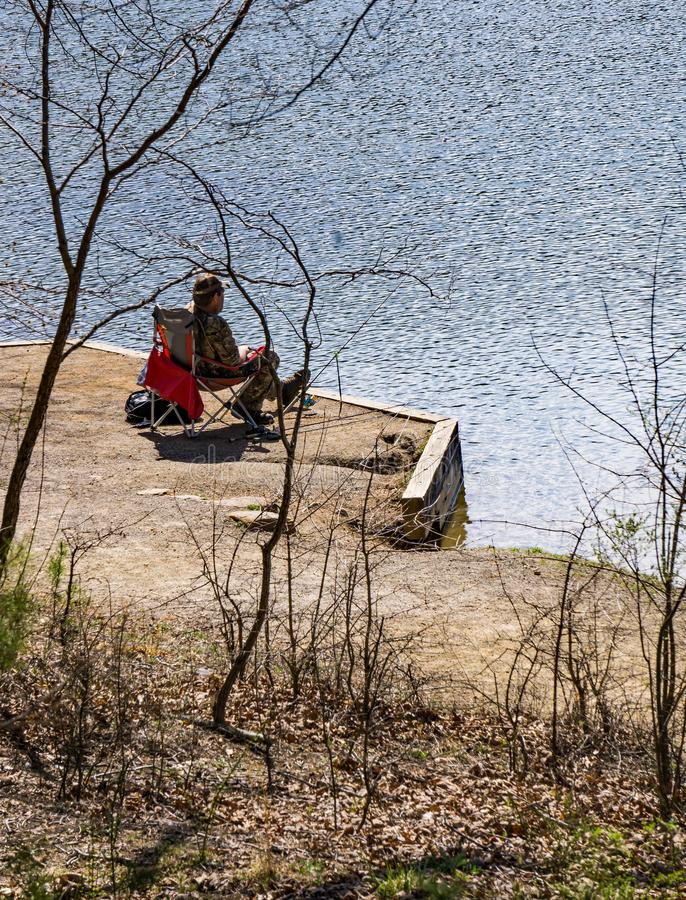 Man Sitting by Lake Fishing for Trout at Pandapas Pond. Giles County, VA – April 14th: A man sitting by the lake in outdoor chair fishing for trout on a royalty free stock photography