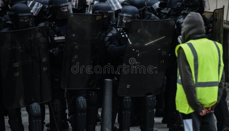 Gilets jaunes - protestations de jaunes de Gilets - protestataire seul se tenant devant la police anti-émeute image stock
