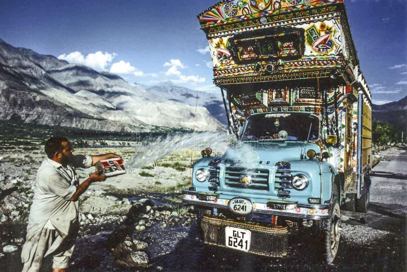 GILGIT, PAQUISTÁN - 1 DE JULIO DE 1987: el hombre limpia el suyo camión terrestre con agua de una cala en Gilgit, Paquistán La ge foto de archivo libre de regalías