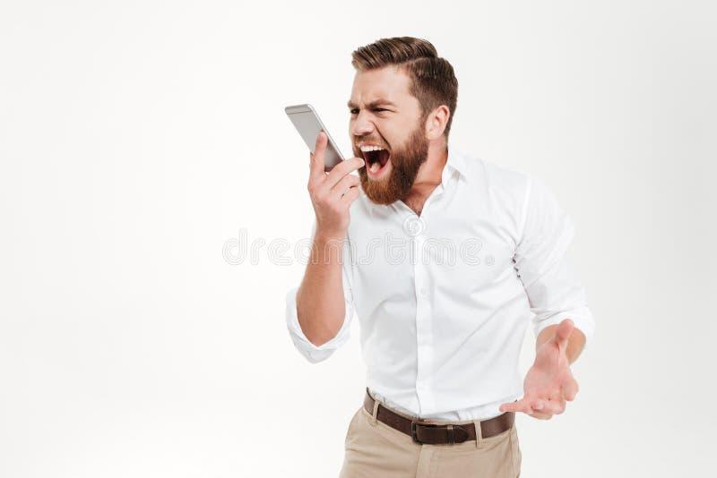 Gillende boze jonge gebaarde emotionele mens die telefonisch spreken stock foto