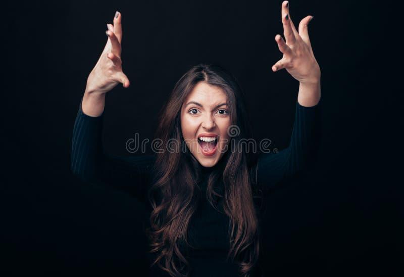 Gillende emotionele boze vrouw met wapens die omhoog op zwarte achtergrond wordt geïsoleerd royalty-vrije stock afbeelding