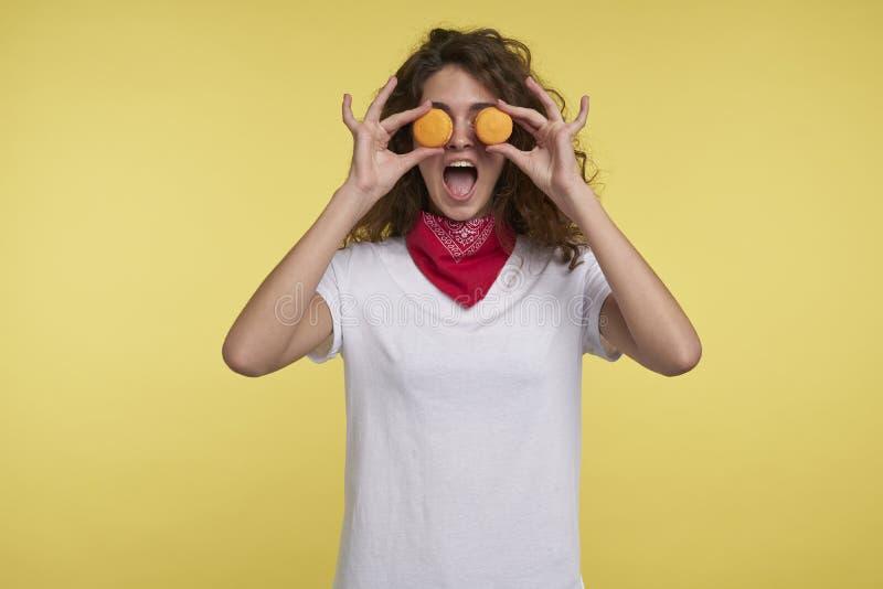 Gillende gelukkige vrouw met makarons, over gele achtergrond royalty-vrije stock afbeelding