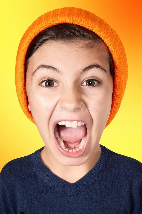 Gillende jonge jongen met groot hoofd op oranje achtergrond stock afbeeldingen