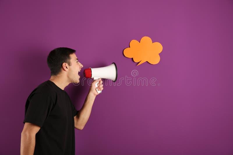 Gillende jonge mens met megafoon dichtbij toespraakbel op kleurenachtergrond stock afbeeldingen