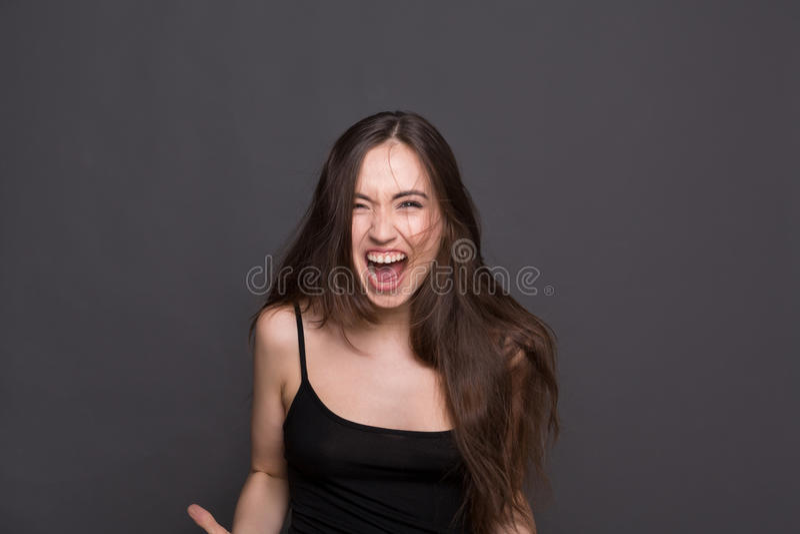 Gillende jonge vrouw die camera bekijkt stock foto