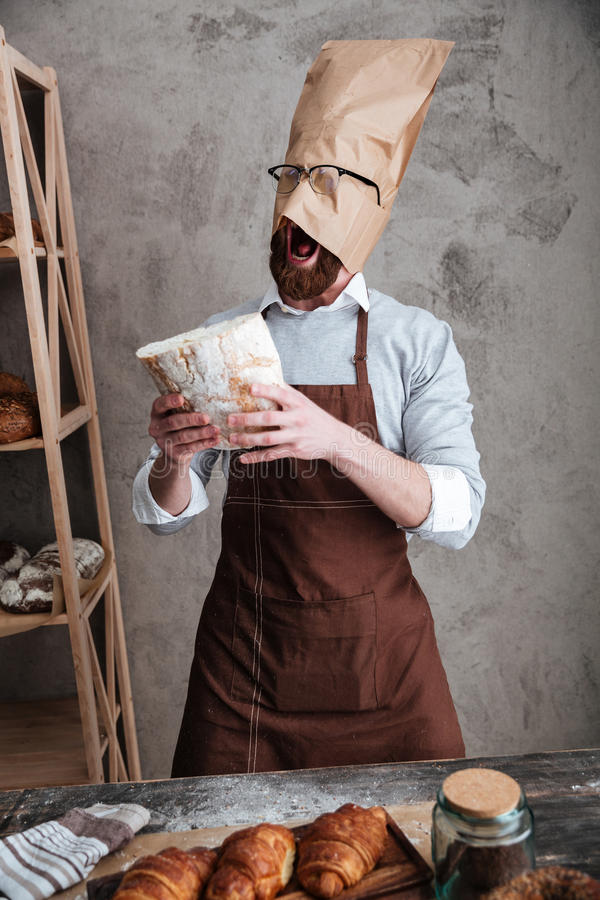 Gillende mensenbakker die zich met document zak op hoofd bevinden royalty-vrije stock fotografie