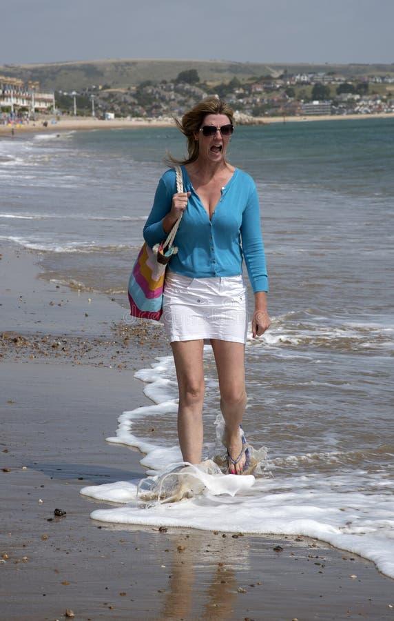 Gillende vrouw aangezien zij zich in koud zeewater bevindt stock afbeeldingen