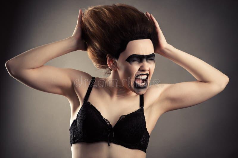 Gillende vrouw met donkere make-up en weelderig haar in bustehouder royalty-vrije stock foto's