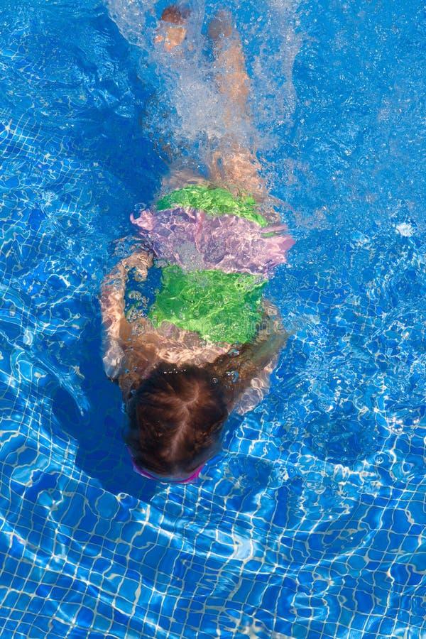 Gilr детей плавая под водой в голубом бассеине стоковое изображение