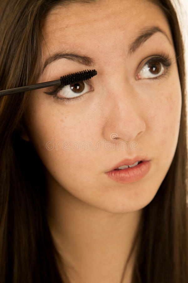 Gilr de l'adolescence de beauté américaine asiatique appliquant son mascara photo libre de droits