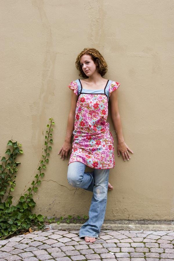 Gilr teenager che si appoggia sulla parete fotografia stock