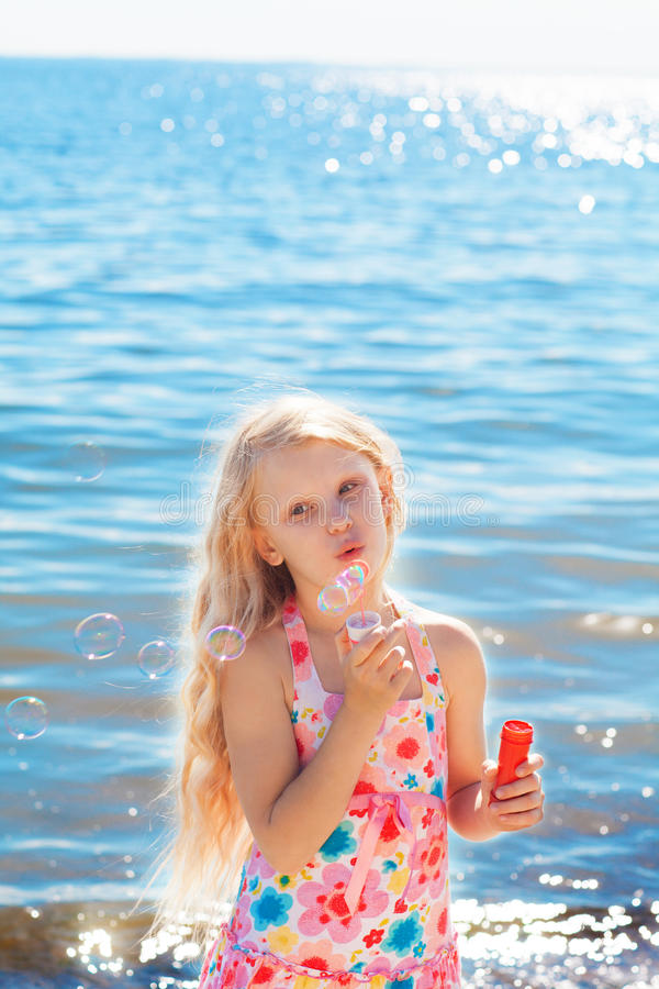 Gilrl avec des bulles de savon sur le bord de la mer image libre de droits