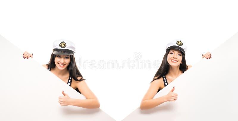 Gils hermosos y atractivos del marinero que sostienen banderas fotos de archivo libres de regalías