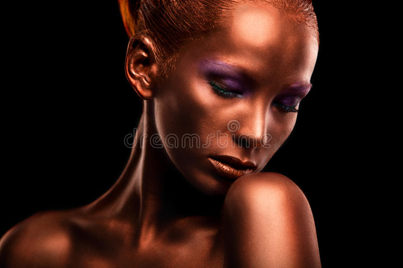 Gilt. Golden Woman's Face Closeup. Futuristic Gilded Make-up. Painted Skin bronze. Gilt. Golden Woman's Face Closeup. Futuristic Gilded Make-up. Painted Skin royalty free stock image