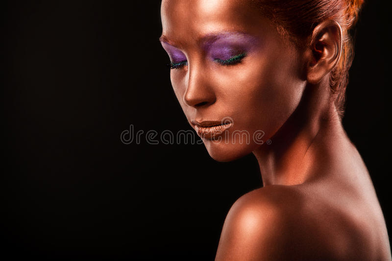 Gilt. Golden Woman's Face Closeup. Futuristic Gilded Make-up. Painted Skin bronze. stock photo