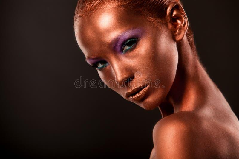 gilt Guld- kvinnas framsidaCloseup Futuristiskt förgyllt smink Målad hudbrons fotografering för bildbyråer