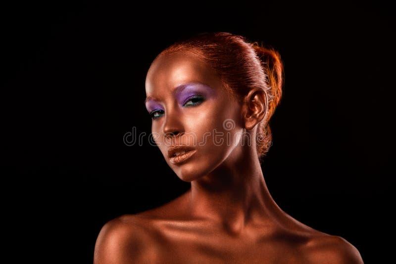 gilt Guld- kvinnas framsidaCloseup Futuristiskt förgyllt smink Målad hudbrons arkivbilder