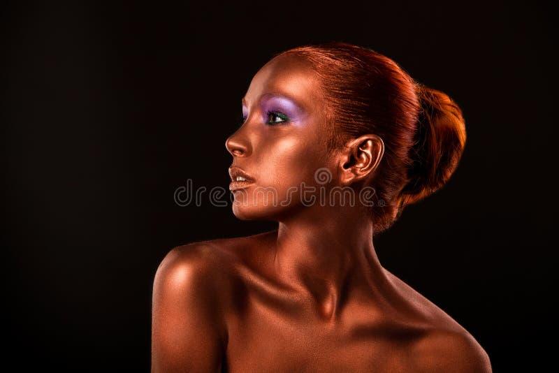 gilt Guld- kvinnas framsidaCloseup Futuristiskt förgyllt smink Målad hudbrons royaltyfri foto