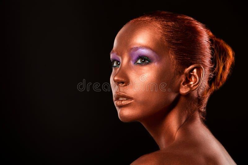 gilt Guld- kvinnas framsidaCloseup Futuristiskt förgyllt smink Målad hudbrons royaltyfri fotografi