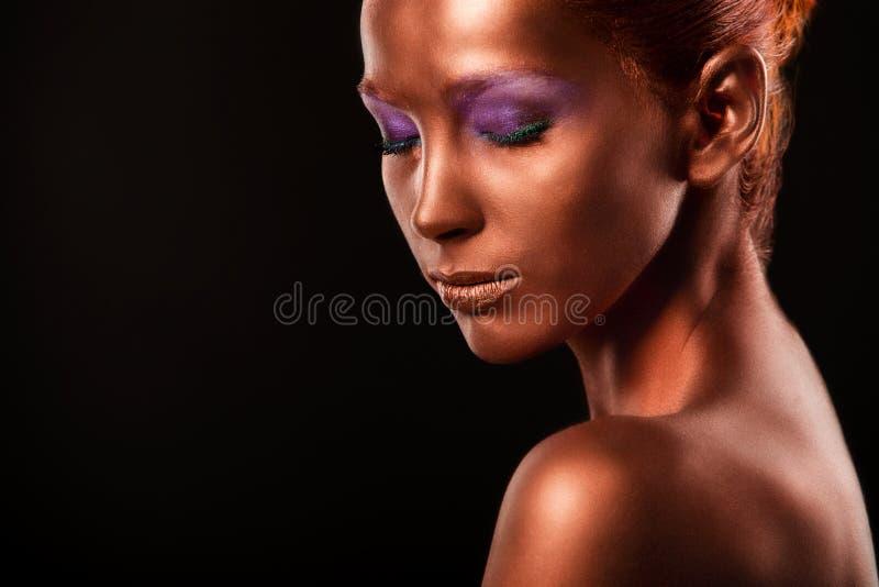 gilt Guld- kvinnas framsidaCloseup Futuristiskt förgyllt smink Målad hudbrons arkivfoto