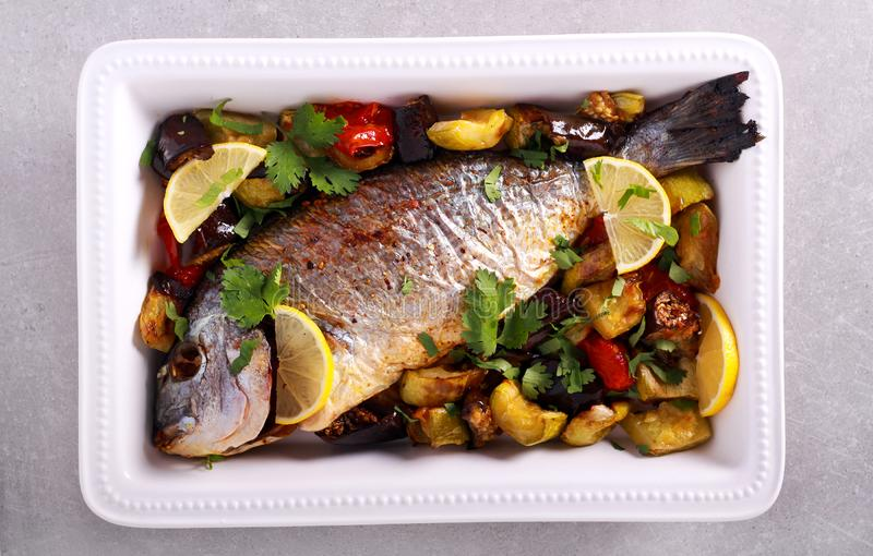 Gilt-head sea bream fish baked. With vegetables stock image
