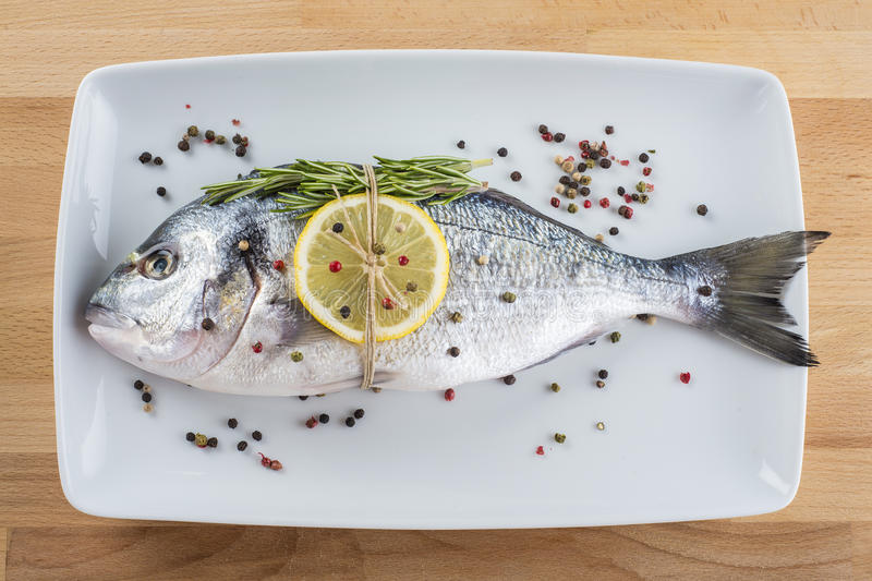 Gilt-head sea bream fish with spices on a platter. Raw gilt-head sea bream fish with spices and herbs on a platter royalty free stock photo