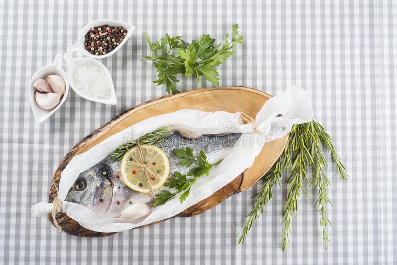 Gilt-head sea bream prepared to be cooked. Raw gilt-head sea bream with herbs and spices in a bakery release paper prepared to be cooked stock image
