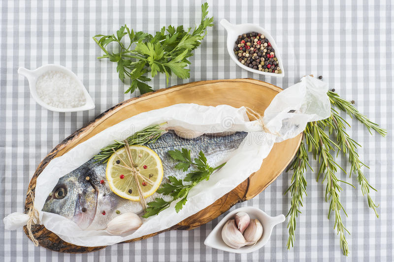 Gilt-head sea bream prepared to be cooked. Raw gilt-head sea bream with herbs and spices in a bakery release paper prepared to be cooked royalty free stock photos