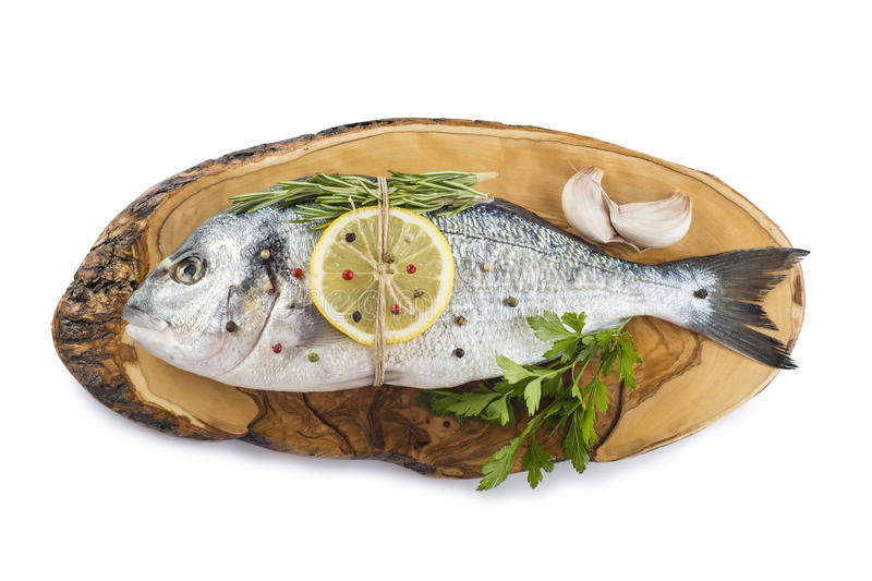 Gilt-head sea bream with spices and herbs. Raw gilt-head sea bream with spices and herbs on a cutting board ready to be cooked royalty free stock images